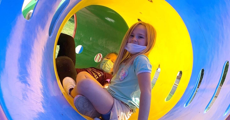 Girl in playground tube