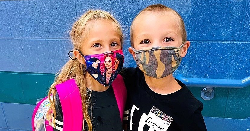 Boy and girl arm in arm masked