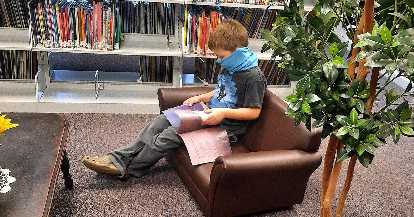 Masked boy on couch reading book