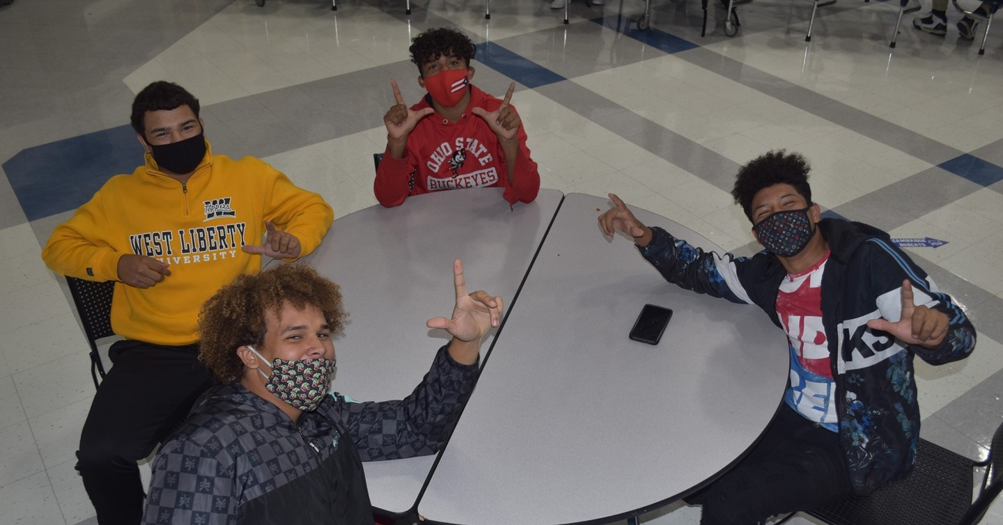 4 boys at table in cafeteria