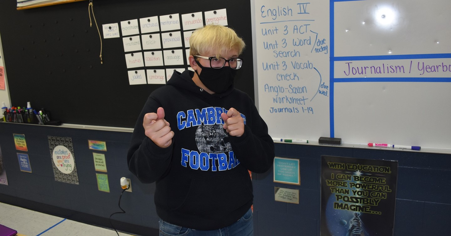 masked boy in front of white board