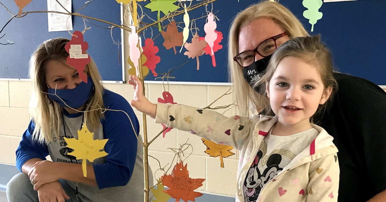 OT therapist with preschool student and thankful tree