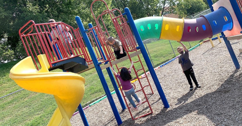 Children play on playground equipment