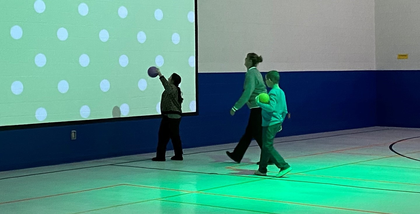 Interactive screen being used by two students and a teacher