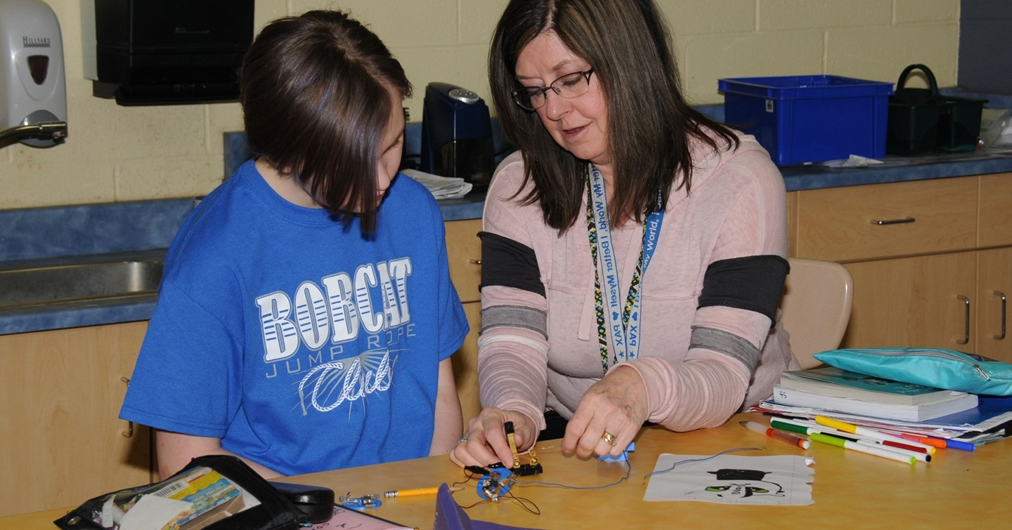 Cambridge Intermediate student and teacher work on project at desk