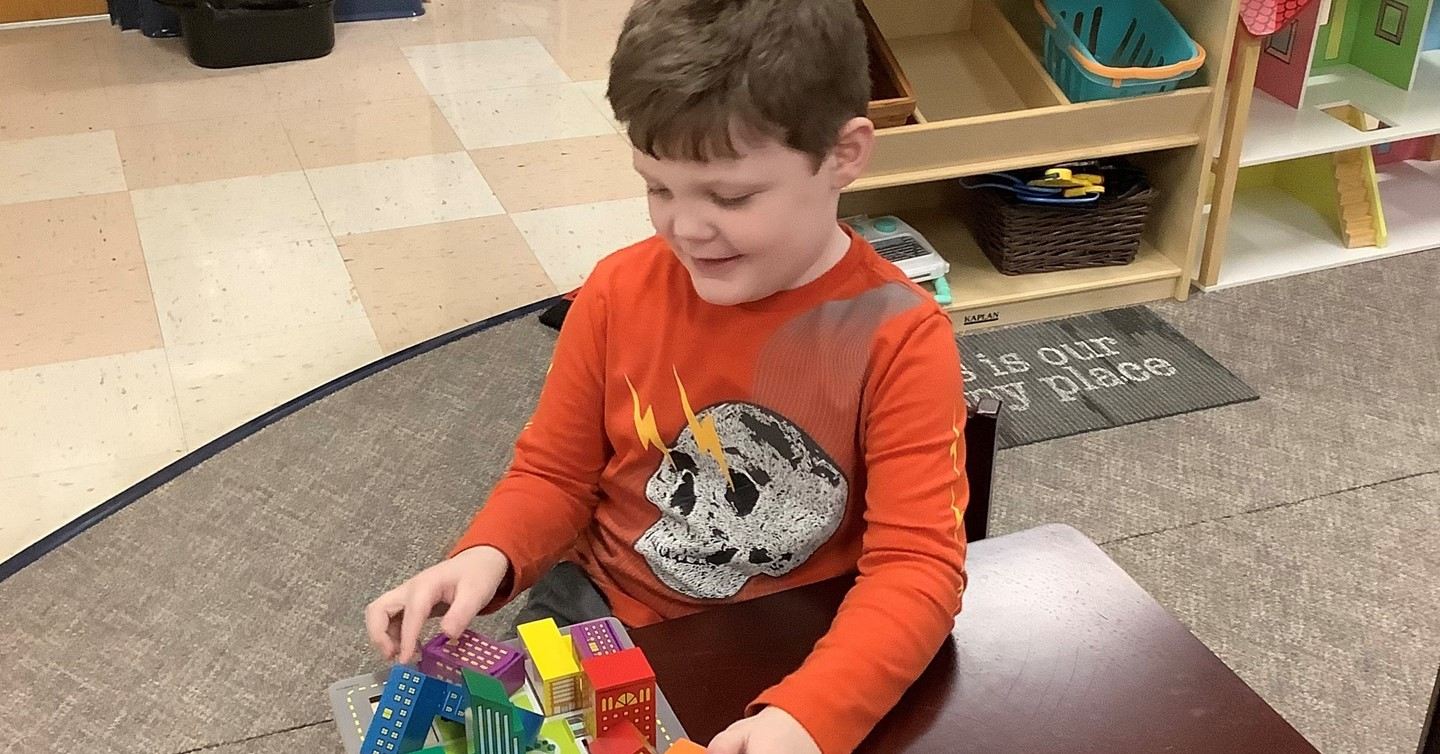 Preschool boy works on game at table