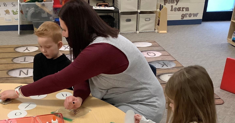 Preschool teacher works with students