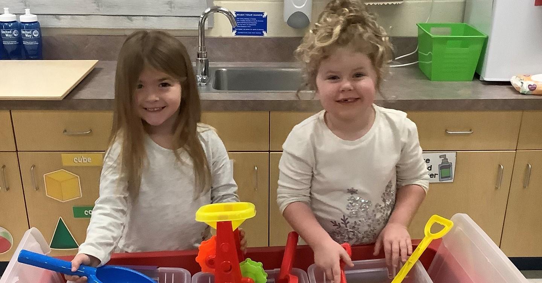 Preschool girls at play kitchen