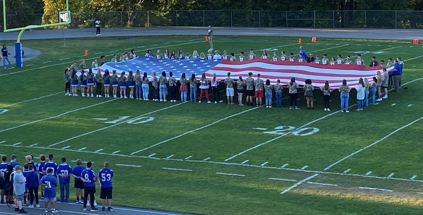 Students hold the flag on military appreciation night