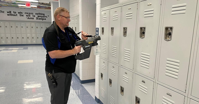 Mr. Pointer sanitizing lockers at Cambridge Middle School